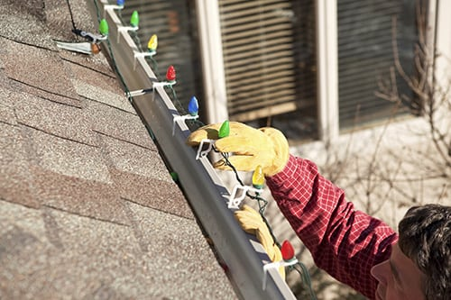 Man Installing LED Christmas Lights On Roof Rain Gutter Great Ideas